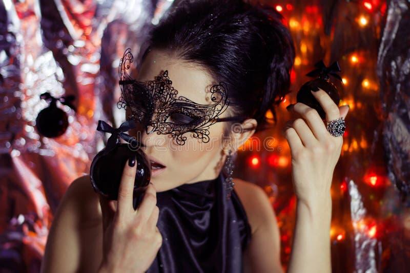 Jovem mulher misteriosa na máscara preta com decorações do Natal imagem de stock royalty free