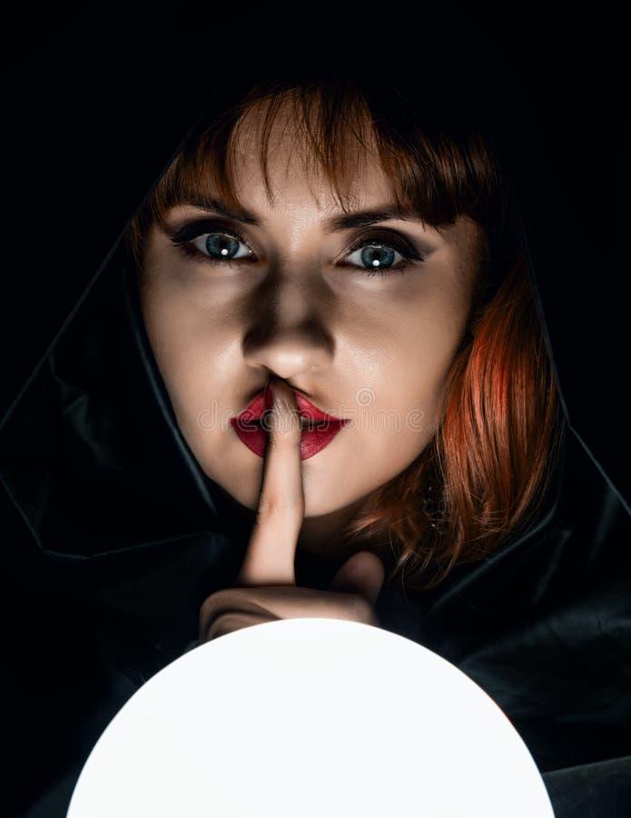 A jovem mulher misteriosa quer saber em uma grande bola luminosa e aumentou um dedo para seus bordos Em um fundo escuro imagem de stock