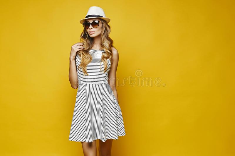 A jovem mulher modelo loura 'sexy' e sensual com bordos 'sexy', no branco listrou o vestido, o chapéu e os óculos de sol, ajustan fotos de stock