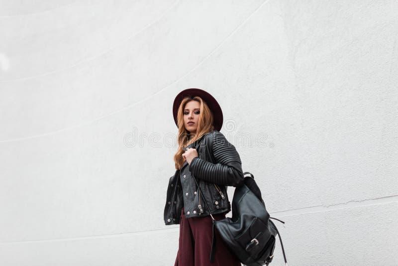 Jovem mulher moderna bonita na roupa elegante com uma trouxa de couro preta em um chap?u roxo que levanta perto de uma parede bra fotografia de stock