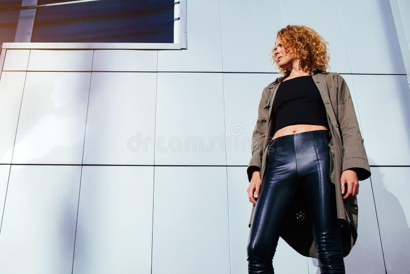 Jovem mulher moderna com o cabelo encaracolado vermelho que está contra a parede cinzenta Equipamento à moda vestindo modelo do v imagem de stock