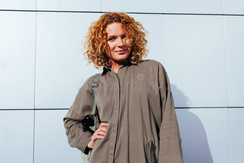 Jovem mulher moderna com o cabelo encaracolado vermelho que está contra a parede cinzenta Modelo do moderno que veste o equipamen fotografia de stock royalty free