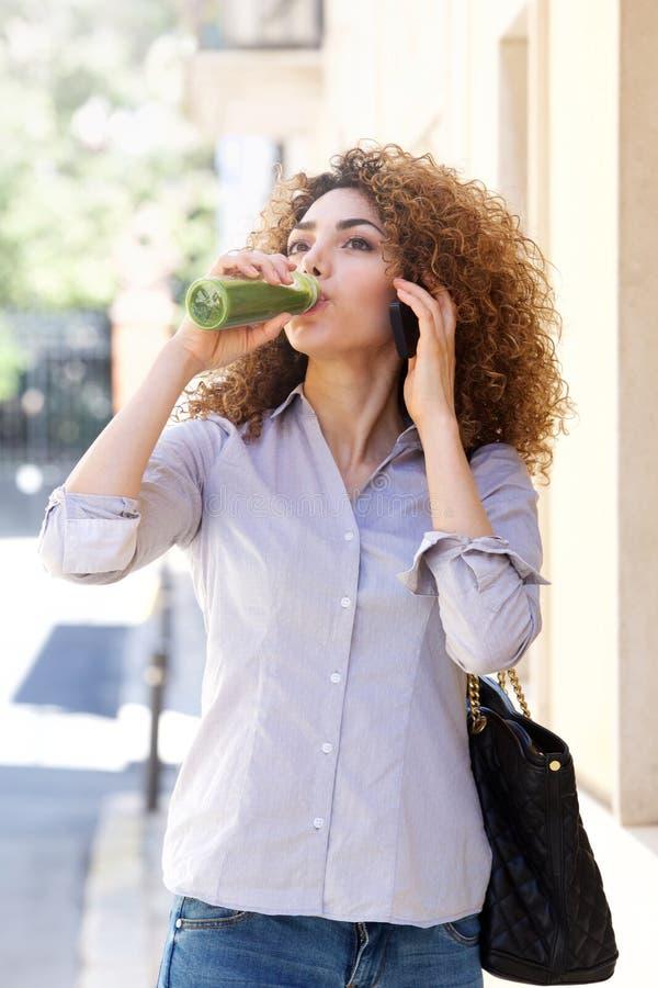 Jovem mulher moderna que anda com telefone celular e suco bebendo foto de stock