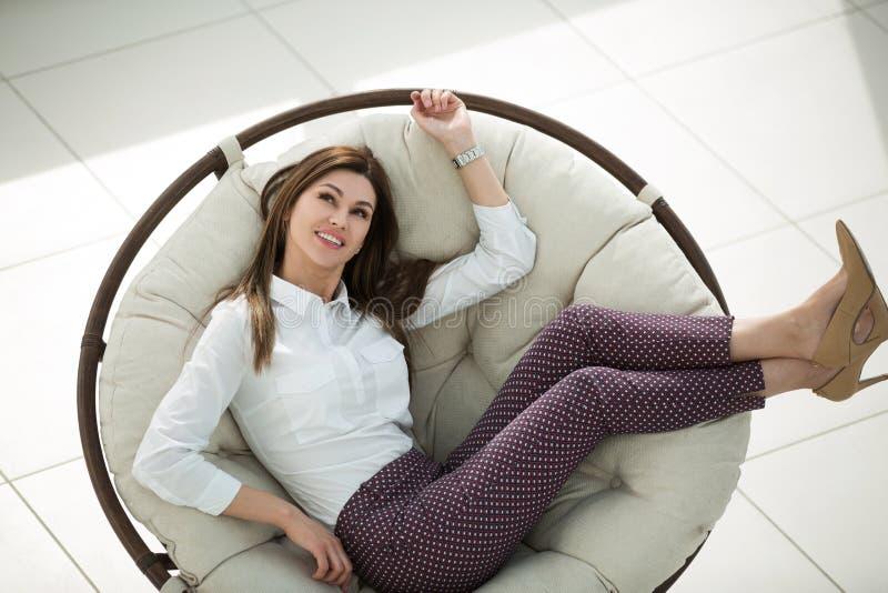 Jovem mulher moderna que senta-se na cadeira redonda confortável imagens de stock