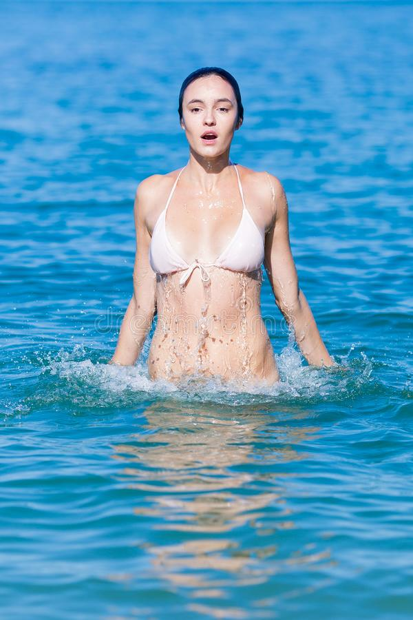 A jovem mulher molhada no biquini salta da água fotos de stock royalty free