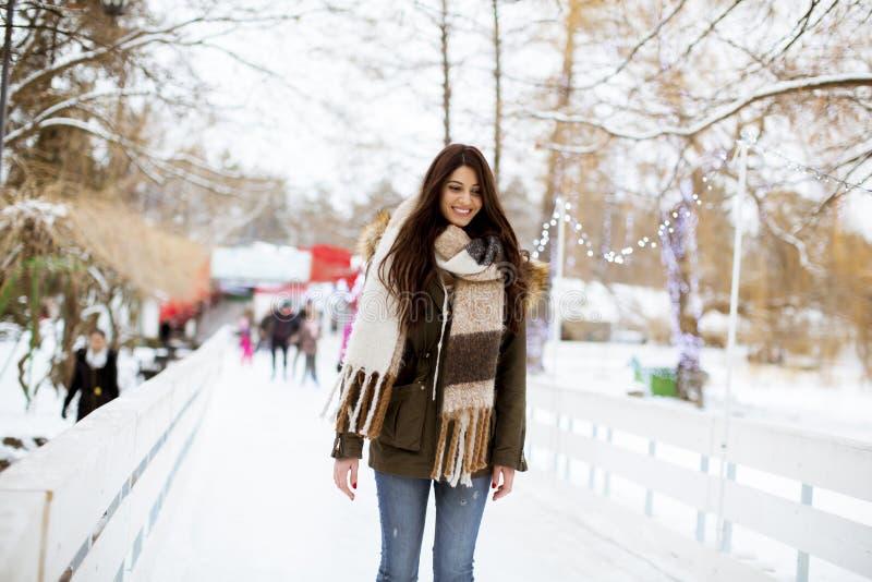 A jovem mulher monta patins de gelo no parque imagem de stock
