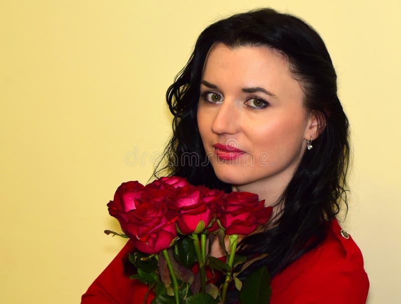 A jovem mulher a morena em um vestido vermelho com rosas vermelhas fotografia de stock
