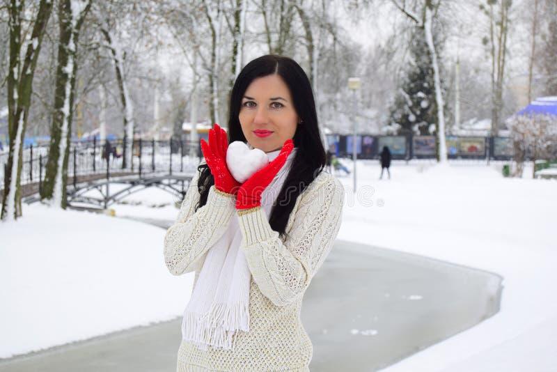 A jovem mulher a morena guarda uma bola de neve sob a forma do coração fotos de stock