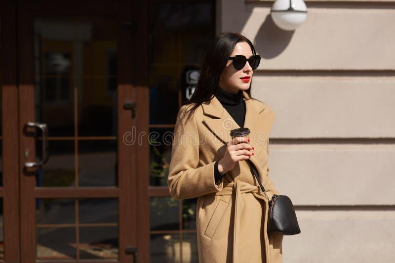 A jovem mulher moreno bonita guarda a xícara de café em suas mãos, caminhadas ao longo das ruas sunlighted, veste a mostarda eleg fotos de stock royalty free