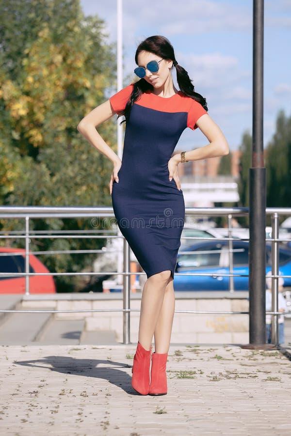 A jovem mulher moreno bonita no vestido azul e vermelho, vermelho vestindo alto-colocou saltos sapatas, óculos de sol, andando ao imagem de stock