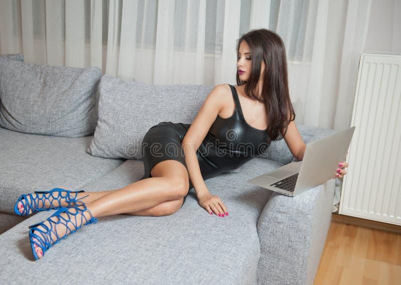 Jovem mulher moreno 'sexy' que veste o vestido curto de couro preto que senta-se na cama e que olha no portátil Menina sensual imagens de stock