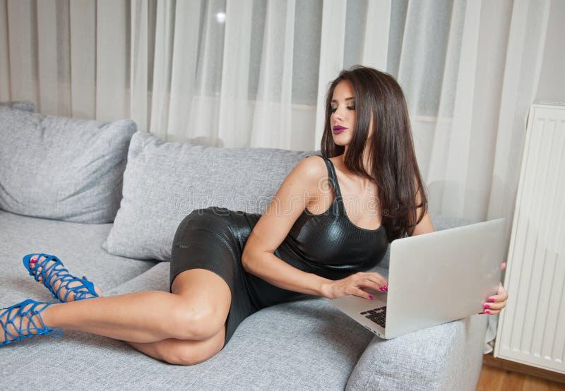 Jovem mulher moreno 'sexy' que veste o vestido curto de couro preto que senta-se na cama e que olha no portátil foto de stock royalty free