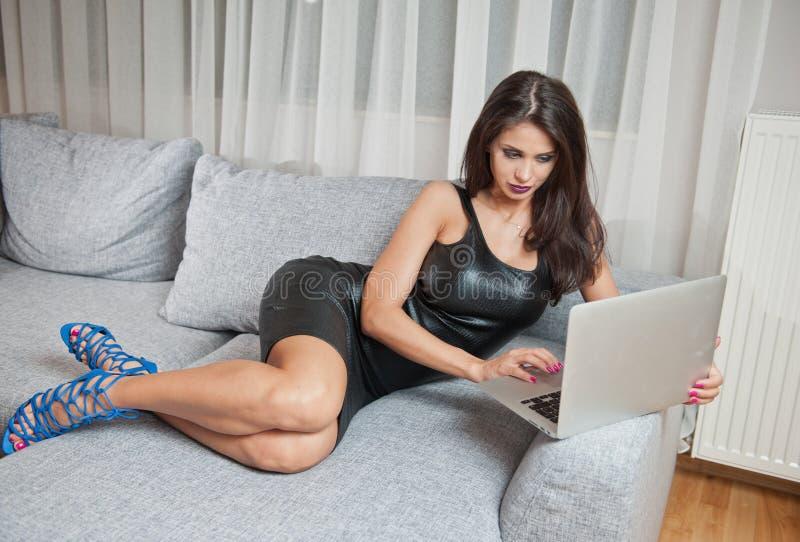 Jovem mulher moreno 'sexy' que veste o vestido curto de couro preto que senta-se na cama e que olha no portátil imagens de stock royalty free