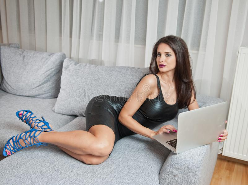 Jovem mulher moreno 'sexy' que veste o vestido curto de couro preto que senta-se na cama e que olha no portátil imagem de stock royalty free