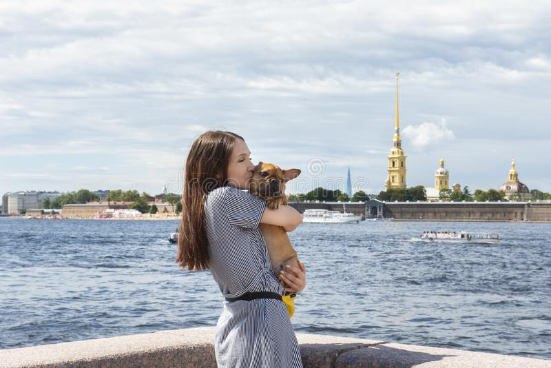 A jovem mulher mostra o passeio do cachorrinho do buldogue francês imagens de stock
