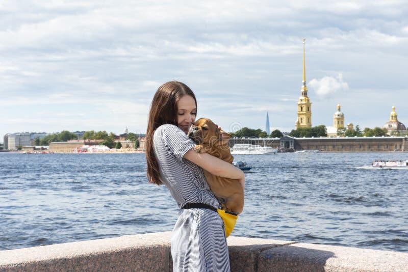 A jovem mulher mostra o passeio do cachorrinho do buldogue francês imagens de stock royalty free