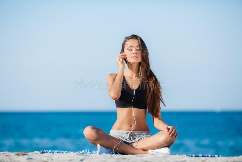 A jovem mulher move o treinamento em uma praia fotografia de stock royalty free