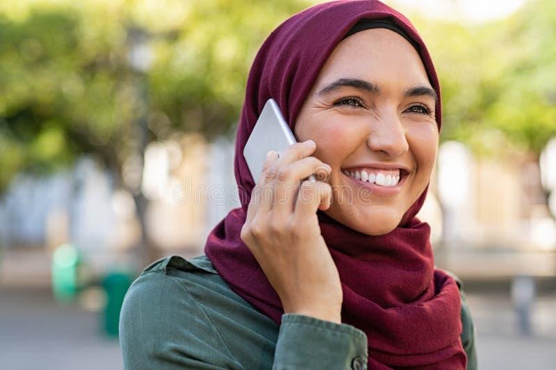 Jovem mulher muçulmana que fala no telefone imagens de stock royalty free