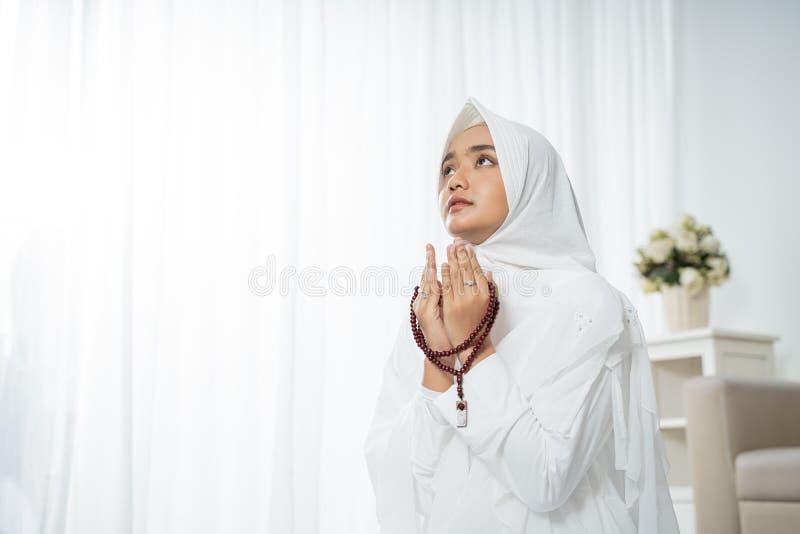 Jovem mulher muçulmana que reza na roupa tradicional branca imagens de stock