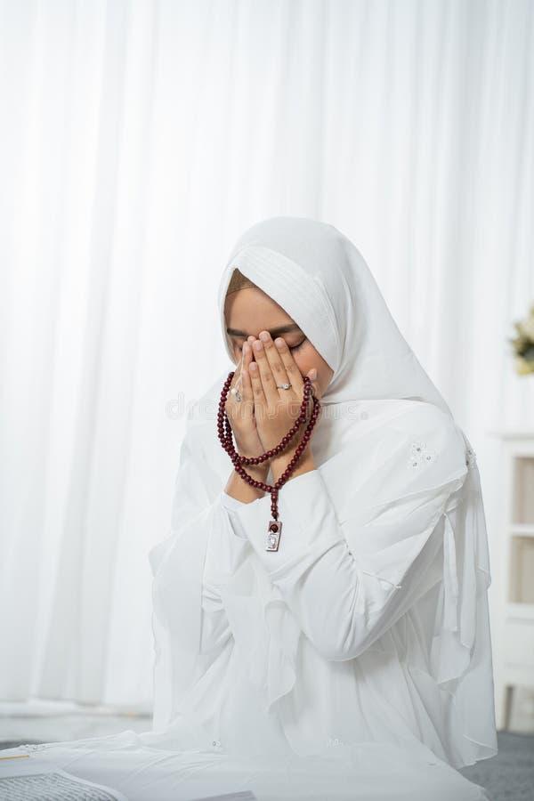 Jovem mulher muçulmana que reza na roupa tradicional branca imagem de stock royalty free