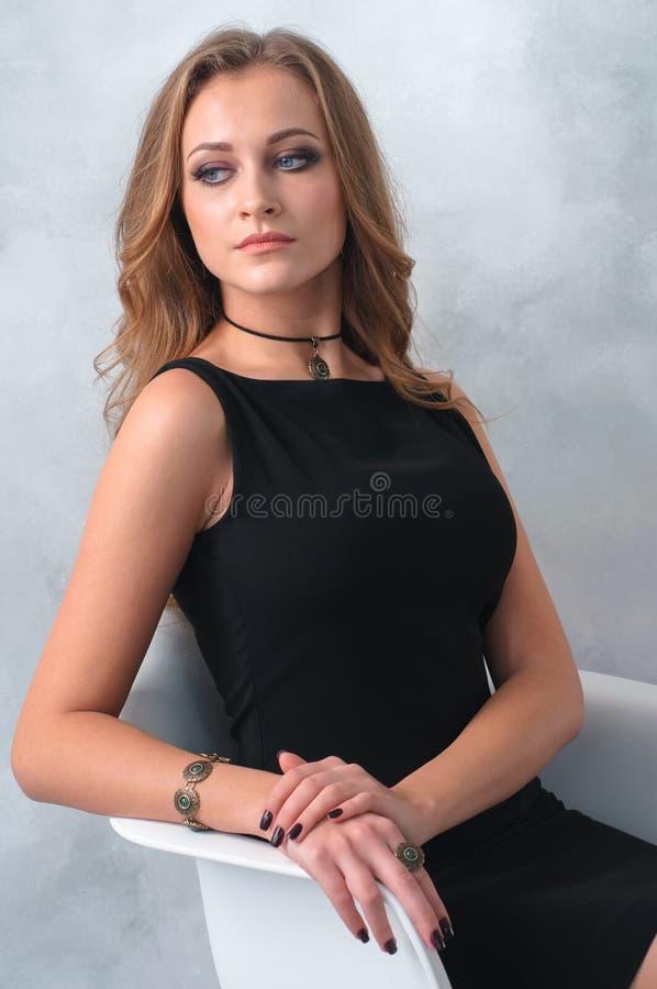 Jovem mulher muito atrativa em um vestido preto com accesso luxuoso foto de stock royalty free