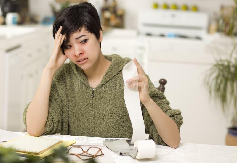 jovem mulher Multi-étnica que agoniza sobre cálculos financeiros imagem de stock