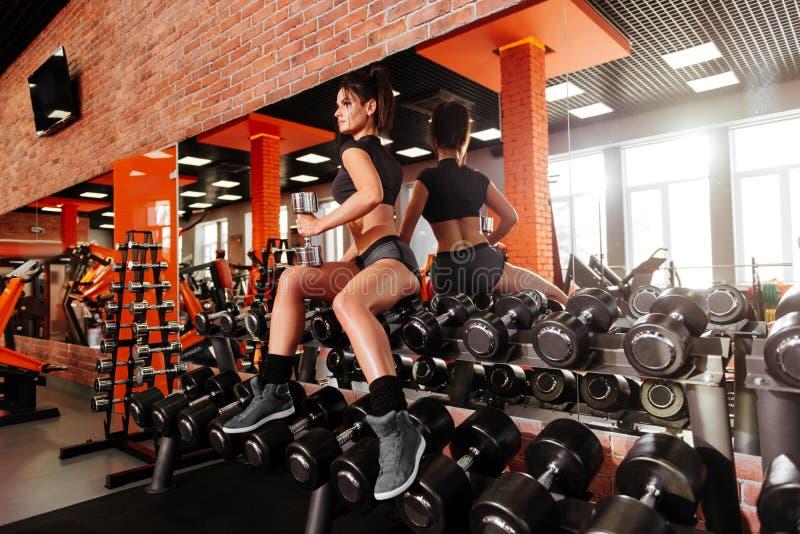 Jovem mulher muscular com o corpo bonito que faz exerc?cios com peso fotografia de stock