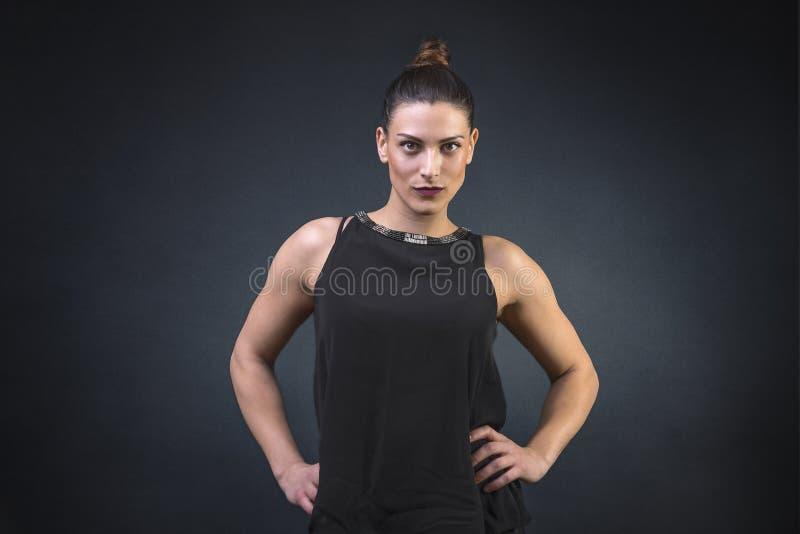 Jovem mulher muscular e atrativa, mostrando fora a sua construção forte o corpo muscular vestido por uma noite para fora fotos de stock royalty free