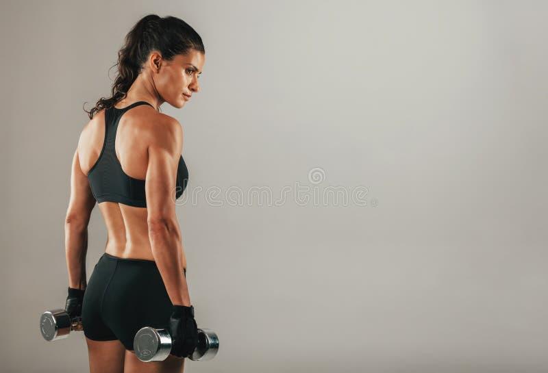 Jovem mulher muscular forte que guarda pesos fotografia de stock royalty free
