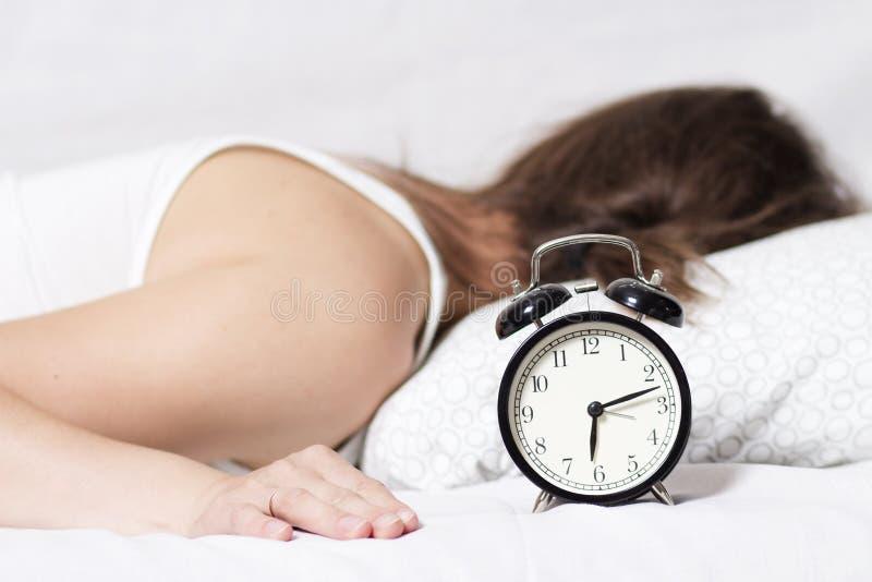 A jovem mulher não ouve a soada de um despertador na manhã A menina não quer levantar-se cedo na manhã para trabalhar foto de stock