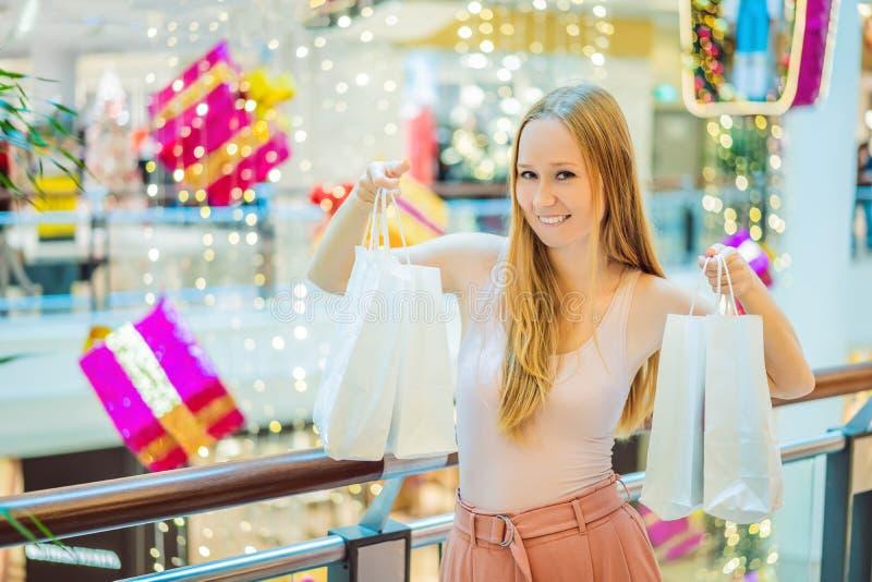 Jovem mulher na alameda do Natal com compra do Natal Bu da beleza imagens de stock royalty free