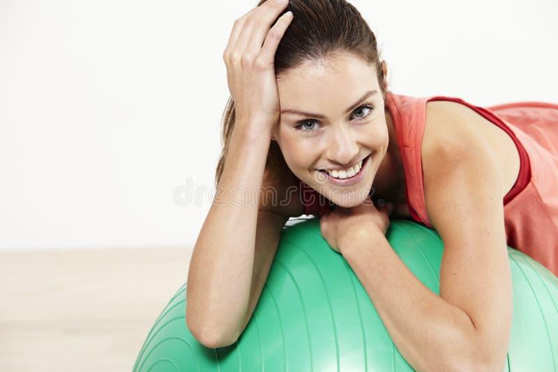 Jovem mulher na bola dos pilates foto de stock