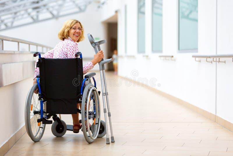 Jovem mulher na cadeira de rodas no centro médico fotos de stock