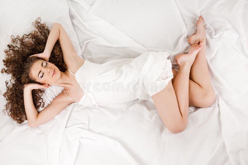 Jovem mulher na cama fotos de stock royalty free