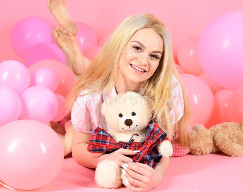 Jovem mulher na cama que abraça o urso de peluche Conceito da menina do aniversário Louro na cara de sorriso que relaxa com o bri imagem de stock