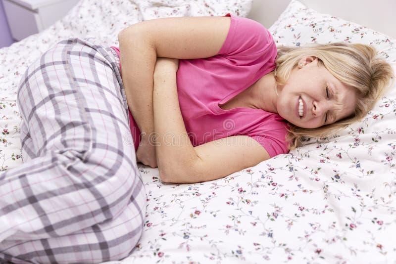 A jovem mulher na cama sofre da dor imagem de stock royalty free
