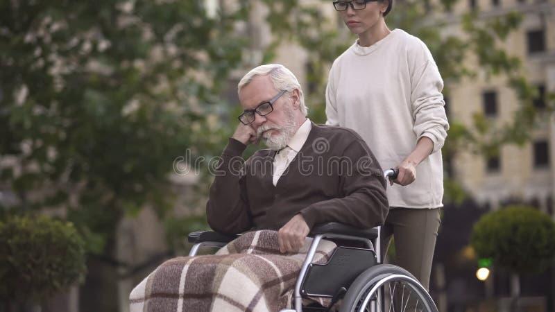 Jovem mulher na caminhada com o pensionista triste na cadeira de rodas, auxílio do cuidador, ajuda imagens de stock royalty free