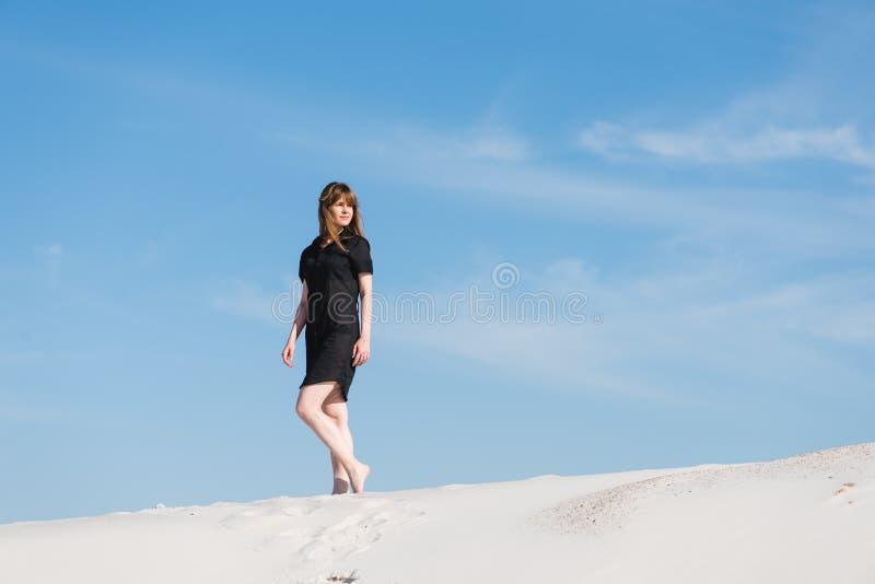 Jovem mulher na caminhada preta do vestido em dunas de areia fotos de stock royalty free