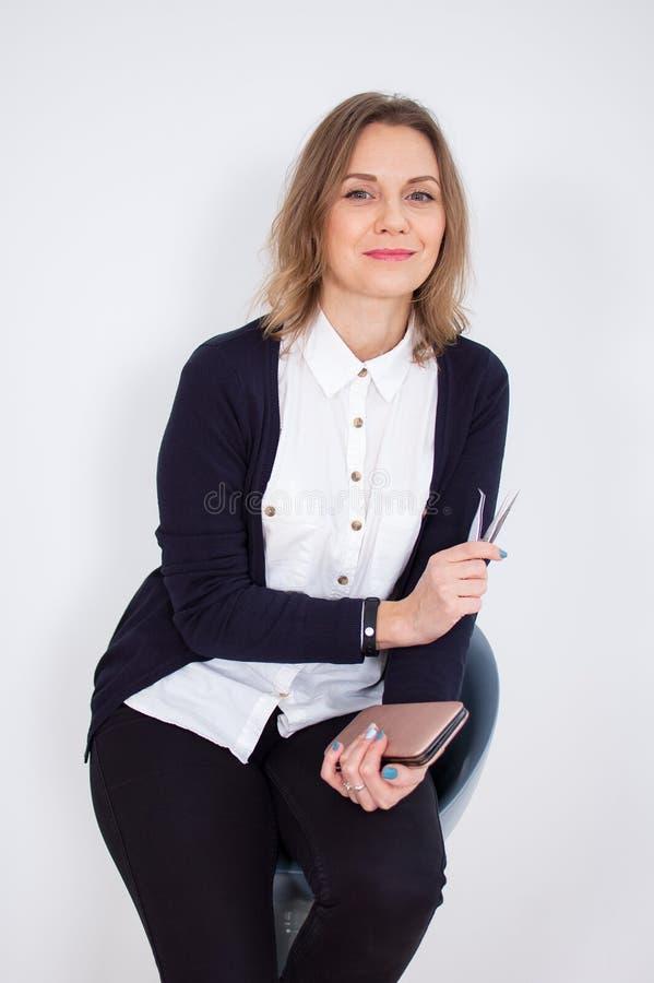 A jovem mulher na camisa e em calças pretas está guardando a pinça da sobrancelha em suas mãos ao sentar-se na cadeira no estúdio imagem de stock royalty free
