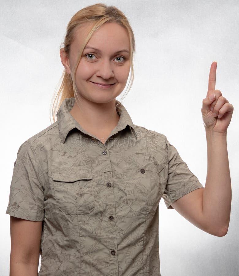 Jovem mulher na camisa trekking que aponta acima fotografia de stock