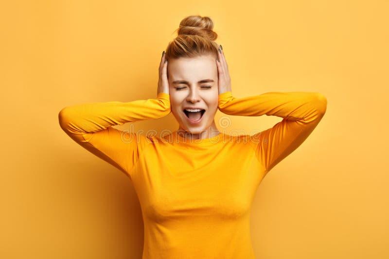 Jovem mulher na camiseta amarela à moda que grita no terror com mãos em suas orelhas imagem de stock royalty free