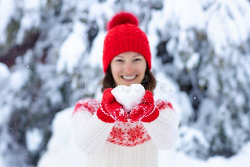 Jovem mulher na camiseta feita malha que guarda a bola da neve da forma do coração no inverno Menina no jogo da luta da neve da f imagens de stock