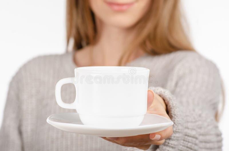Jovem mulher na camiseta que guarda um copo e uns pires brancos nas mãos, café quente bebendo imagens de stock