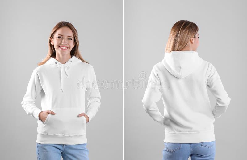 Jovem mulher na camiseta vazia do hoodie em opiniões claras do fundo, as dianteiras e as traseiras imagens de stock royalty free