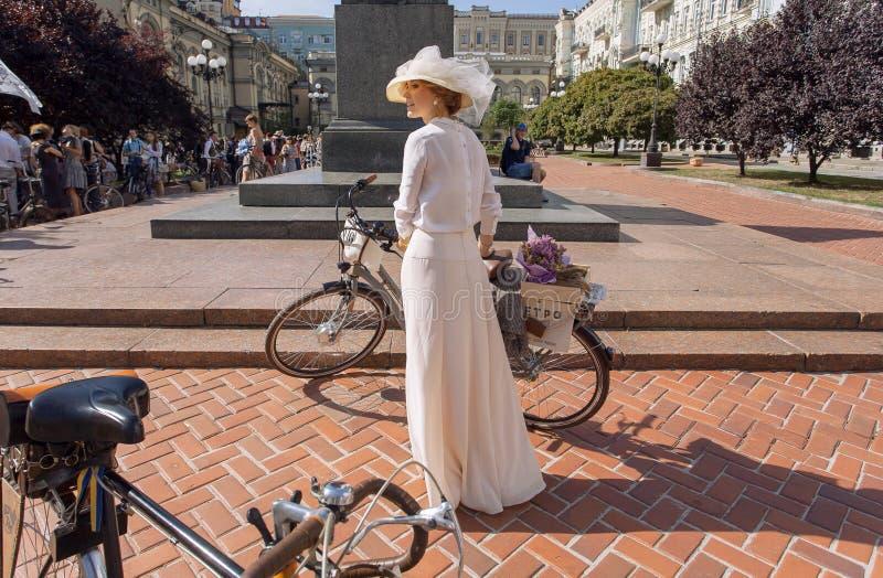 Jovem mulher na ciclagem indo do vestido bonito do vintage durante o cruzeiro retro do festival fotografia de stock royalty free