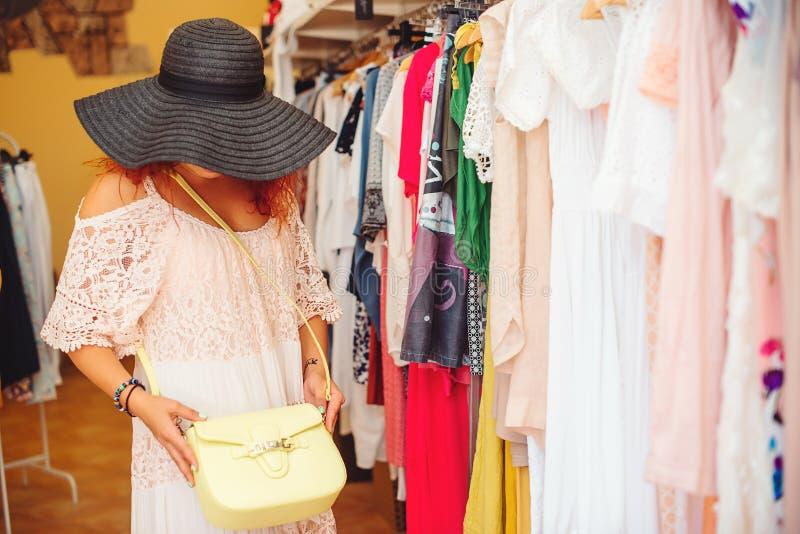 Jovem mulher na compra do chapéu negro na loja das mulheres Tempo da compra Venda do verão foto de stock royalty free