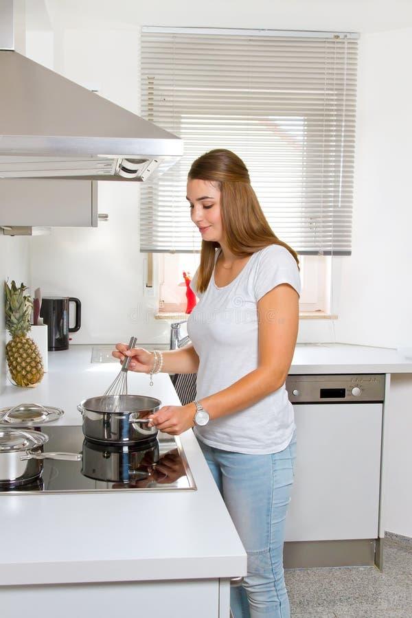 Jovem mulher na cozinha imagens de stock