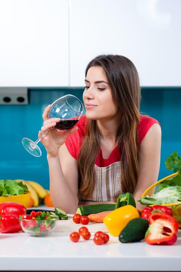 Jovem mulher na cozinha com um vidro de vinho imagens de stock royalty free