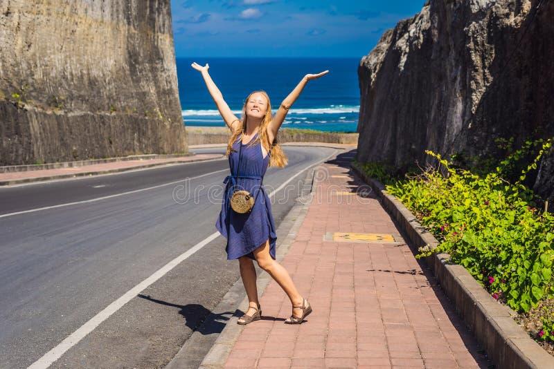 Jovem mulher na estrada à praia Pandawa, DUA de Nusa, Bali, Indone fotografia de stock