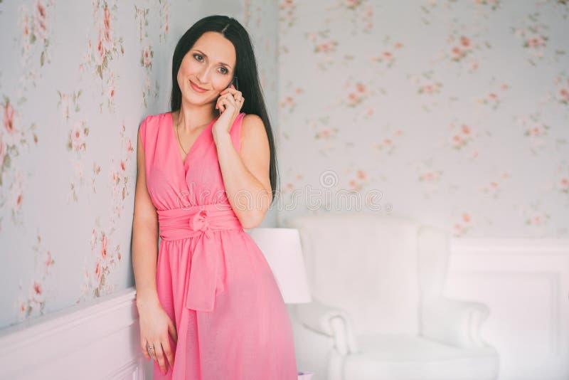 Jovem mulher na fala do telefone celular do vestido da rosa Chamada de Smartphone Sorriso e conversa da menina com telefone celul foto de stock